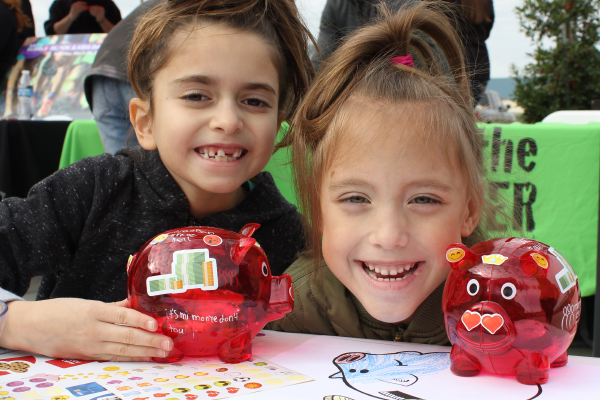 Two kids with decorated MCCU piggy banks